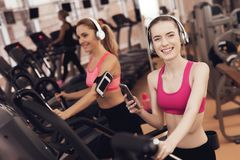 Mother and daughter running on treadmill at the gym. They look happy, fashionable and fit. royalty free stock images