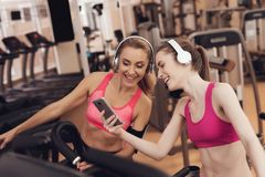 Mother and daughter running on treadmill at the gym. They look happy, fashionable and fit. stock images