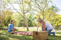 Mother and daughter spreading the picnic blanket. In park Royalty Free Stock Images