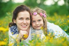 Mother and daughter on spring meadow with blooming flowers stock photos