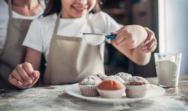 Mother and daughter sprinkling with sugar powder cupcakes Royalty Free Stock Photo