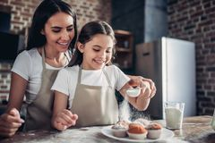 Mother and daughter sprinkling with sugar powder cupcakes stock photos