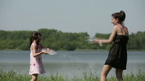 Mother and daughter squirting water reverse speed slow motion stock video footage