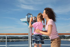 Mother and daughter stand on deck of ship. Girl looks through binoculars at landscape Stock Photography