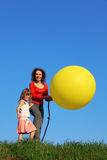 Mother and daughter stand in meadow with balloon Stock Images