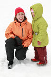 Mother with daughter stand on to snow and laugh Royalty Free Stock Photo