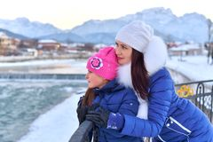 A mother and daughter standing arm in arm on the seafront mountain river in winter. Day stock photos