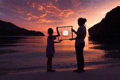 Mother and daughter standing on the beach with red sky sunset Royalty Free Stock Photography