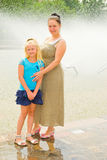 Mother and daughter standing at the fountain Royalty Free Stock Images