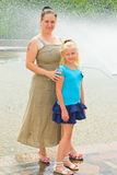 Mother and daughter standing at the fountain Stock Photos
