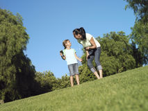 Mother and daughter (6-8) standing on grass in park, girl holding MP3 player, surface level (tilt) Stock Photo