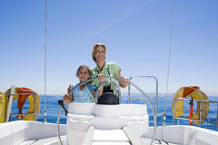 Mother and daughter (8-10) standing at helm of sailing boat out at sea, steering, smiling, front view, portrait Royalty Free Stock Photography