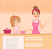 Mother with daughter standing in kitchen Stock Image