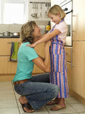 Mother and daughter (6-8) standing in kitchen, girl wearing striped apron, woman tying knot, smiling Stock Images