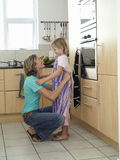 Mother and daughter (6-8) standing in kitchen, girl wearing striped apron, woman tying knot, smiling Stock Photos