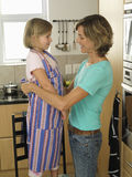 Mother and daughter (6-8) standing in kitchen, girl wearing striped apron, woman tying knot, smiling Royalty Free Stock Photos