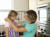 Mother and daughter (6-8) standing in kitchen, girl wearing striped apron, woman tying knot, smiling Stock Photo