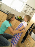 Mother and daughter (6-8) standing in kitchen, girl wearing striped apron, woman tying knot (tilt) Royalty Free Stock Photos