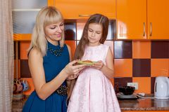 Mother with daughter standing in kitchen Stock Photography
