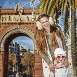Mother and daughter standing near Arc de Triomf. In Barcelona for a perfect winter. Portrait of smiling young mother and daughter near Arc de Triomf in Barcelona Stock Images