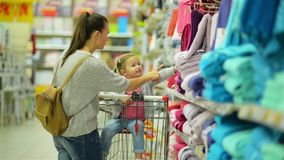 Mother and Daughter Standing near Supermarket Shelf with Baby Clothing and Choosing Something. Shopping Concept. stock footage