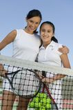 Mother and daughter standing at net on tennis court portrait low angle view Royalty Free Stock Photography