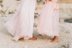 Mother and daughter are standing on a rock in pink dresses. royalty free stock photos