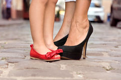 Mother and daughter standing on the sidewalk close to each other. Mom in black shoes with her daughter in red shoes standing on the pavement close to each other Stock Images