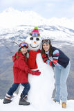 Mother and daughter (7-9) standing by snowman in snow, smiling, portrait, mountain range in background Stock Images