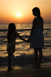 Mother and daughter standing at sunset and looking at each other Stock Photo
