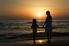 Mother and daughter standing at sunset and looking at each other Stock Images