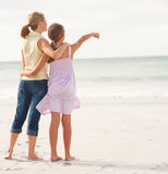 Mother and daughter standing together at beach. Rear view of a mother and teenaged daughter standing on the beach, girl pointing towards the sea Royalty Free Stock Photos