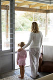 Mother and daughter standing together at home stock images