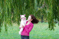 Mother and daughter standing under a colorful willow tree Stock Photos