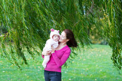 Mother and daughter standing under a colorful willow tree Royalty Free Stock Photos