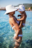 Mother and daughter staying in the sea water. Stock Photos