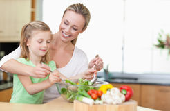 Mother and daughter stirring salad. Together Stock Photos