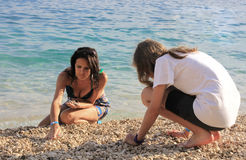 Mother and daughter on stone beach royalty free stock photography