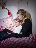 Mother and Daughter storytelling. Sitting on the bed stock photos