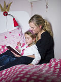 Mother and Daughter storytelling. Sitting in the bed Stock Photos