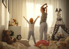 Mother and   daughter stretch themselves after waking up in the Royalty Free Stock Photo