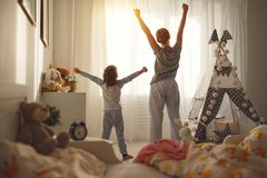 Mother and   daughter stretch themselves after waking up in the Royalty Free Stock Photos