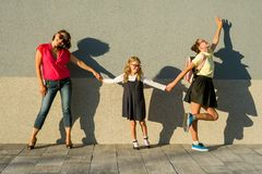 Mother and daughter students holding hands go to school. Royalty Free Stock Photography