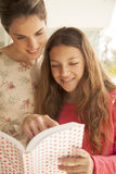 Mother and daughter studying. Mother and daughter reading a book, back to school Stock Photo