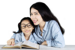 Mother and daughter studying on studio Stock Photography