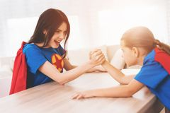 Mother and daughter in suits of superheroes. They compete in arm wrestling royalty free stock photos
