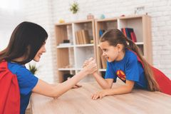 Mother and daughter in suits of superheroes. They compete in arm wrestling royalty free stock photo