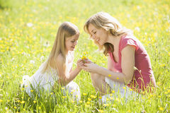 Mother and daughter in summer field. Looking at buttercups Royalty Free Stock Image