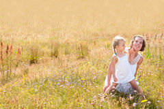 Mother and daughter on a summer meadow Stock Photo
