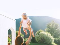 Mother throws baby up, laughing and playing in summer nature royalty free stock photo